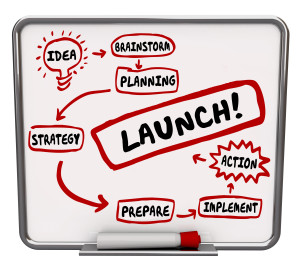 Launch word on a dry erase board with steps for a successful new business start including idea, brainstorm, plan, strategy, prepare, implement, action